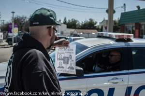 SUFFOLK COUNTY, NY--April 12, 2015--Protester attempts to give Suffolk County Police Officer a leaflet.